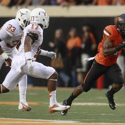 Oklahoma State running back Joseph Randle (1) eludes Texas' Steve Edmond (33) and Adrian Phillips (17) and takes off on a 69-yard touchdown run in the first quarter of an NCAA college football game in Stillwater, Okla., Saturday, Sept. 29, 2012.
