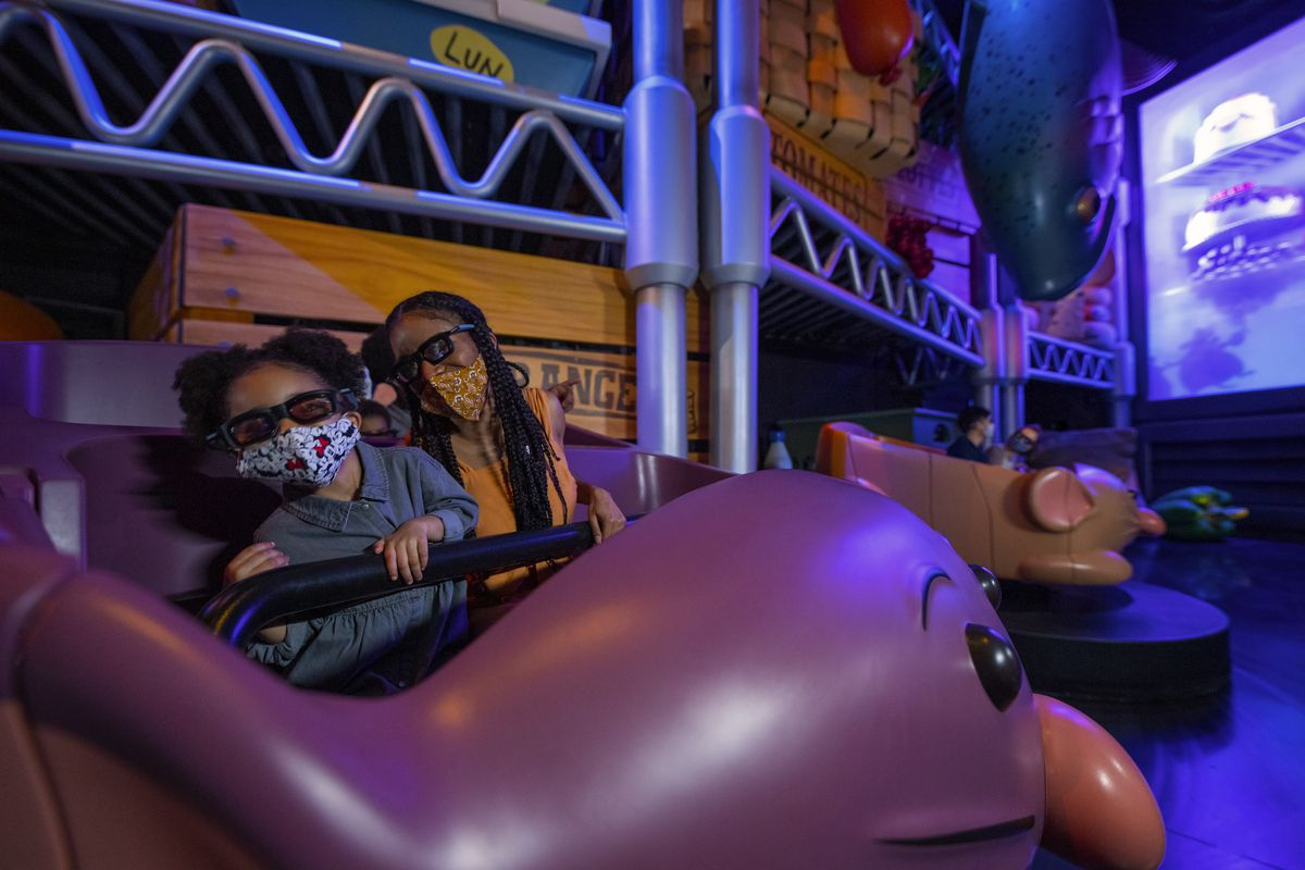 Inside a darkened ride, two children spin in a rat car wearing 3D glasses.
