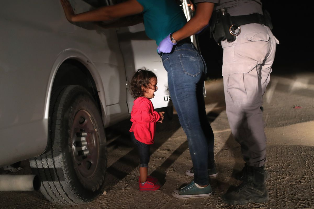 A child cries as her mother is searched and detained by US officials.
