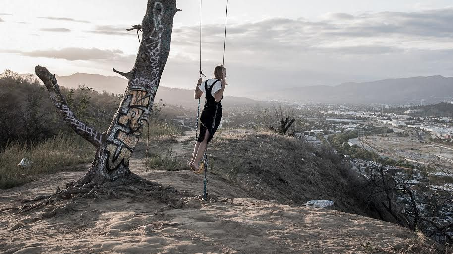 Father's Daughter lookbook image with model wearing overalls on a swing overlooking the city