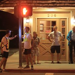 Bill Thompson (2ed L) of Moon Township, Pennsylvania and a support crew member press a crosswalk button to cross the Highway 395 as he passes through the town of Lone Pine after having run more than 100 miles during the AdventurCORPS Badwater 135