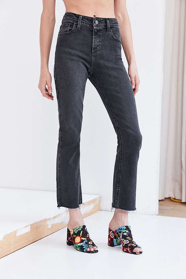 A pair of frayed, flare dark gray jeans