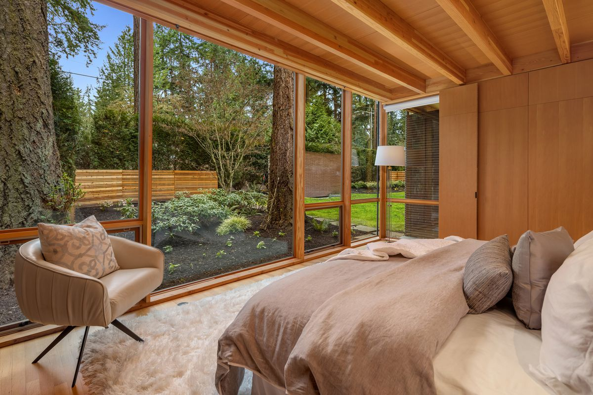 A bedroom has a wall of glass, beamed ceilings, and neutral bedding.
