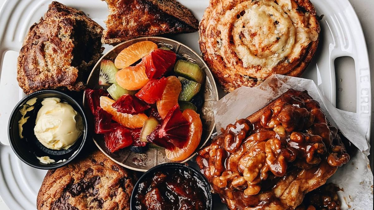 A platter comes stacked with a cookie, a biscuit, a bowl of fruit with various citrus slices and kiwi, a roll, a walnut-miso sticky bun, and a small container of jam. This is the brunch box at Bar King.