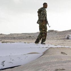 In this photo taken Sunday, Sept. 23, 2012, a Somali government soldier stands over one of the overturned pirate skiffs that litter the dunes on the shoreline near the once-bustling pirate den of Hobyo, Somalia. The empty whisky bottles and overturned, sand-filled skiffs that litter this shoreline are signs that the heyday of Somali piracy may be over - most of the prostitutes are gone, the luxury cars repossessed, and pirates talk more about catching lobsters than seizing cargo ships.
