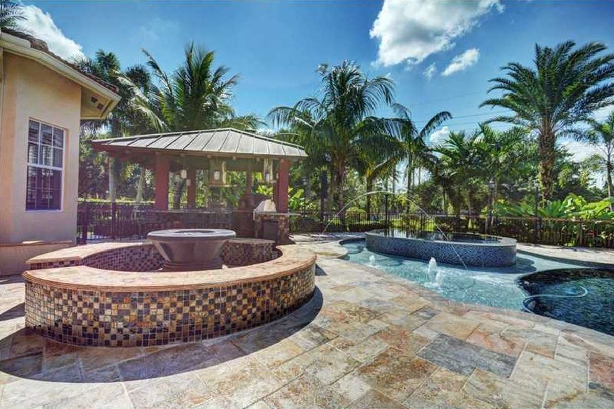 Backyard view of a home in South Florida with a gas fire pit, outdoor kitchen gazebo with a pizza oven, a jacuzzi, pool and palm trees in the background