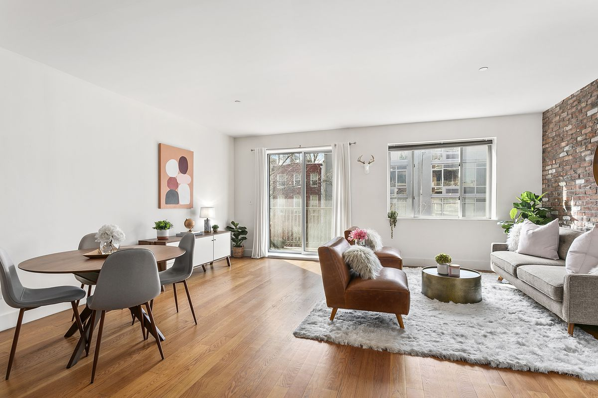 Sliding glass doors open onto a small 10-foot by 5 1/2-foot balcony that overlooks a rear courtyard and neighboring buildings.