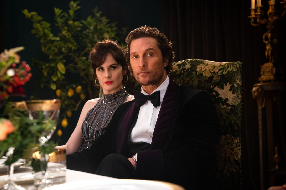 a woman (Michelle Dockery) and a man (Matthew McConaughey) in fancy dress sit at a dinner table in The Gentlemen
