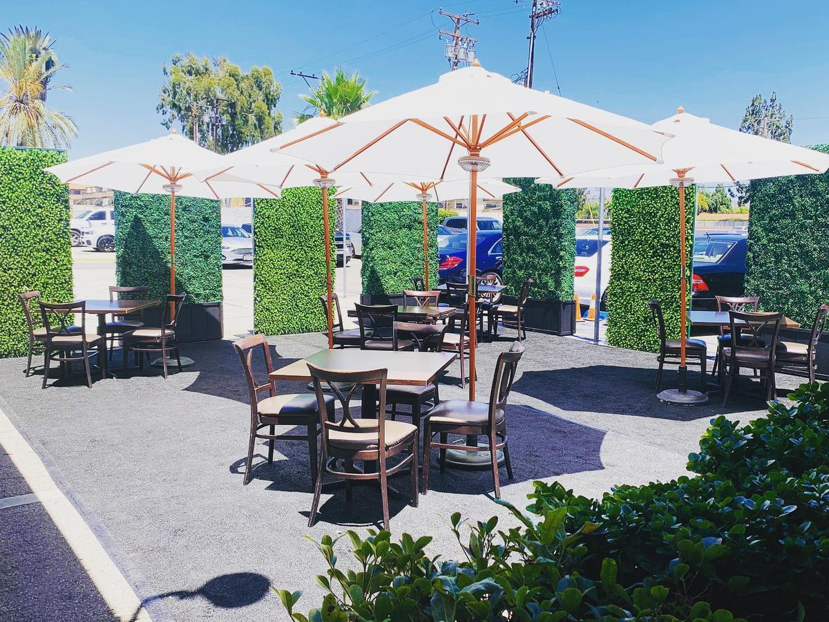 A parking lot outdoor dining set up at an aging steakhouse.