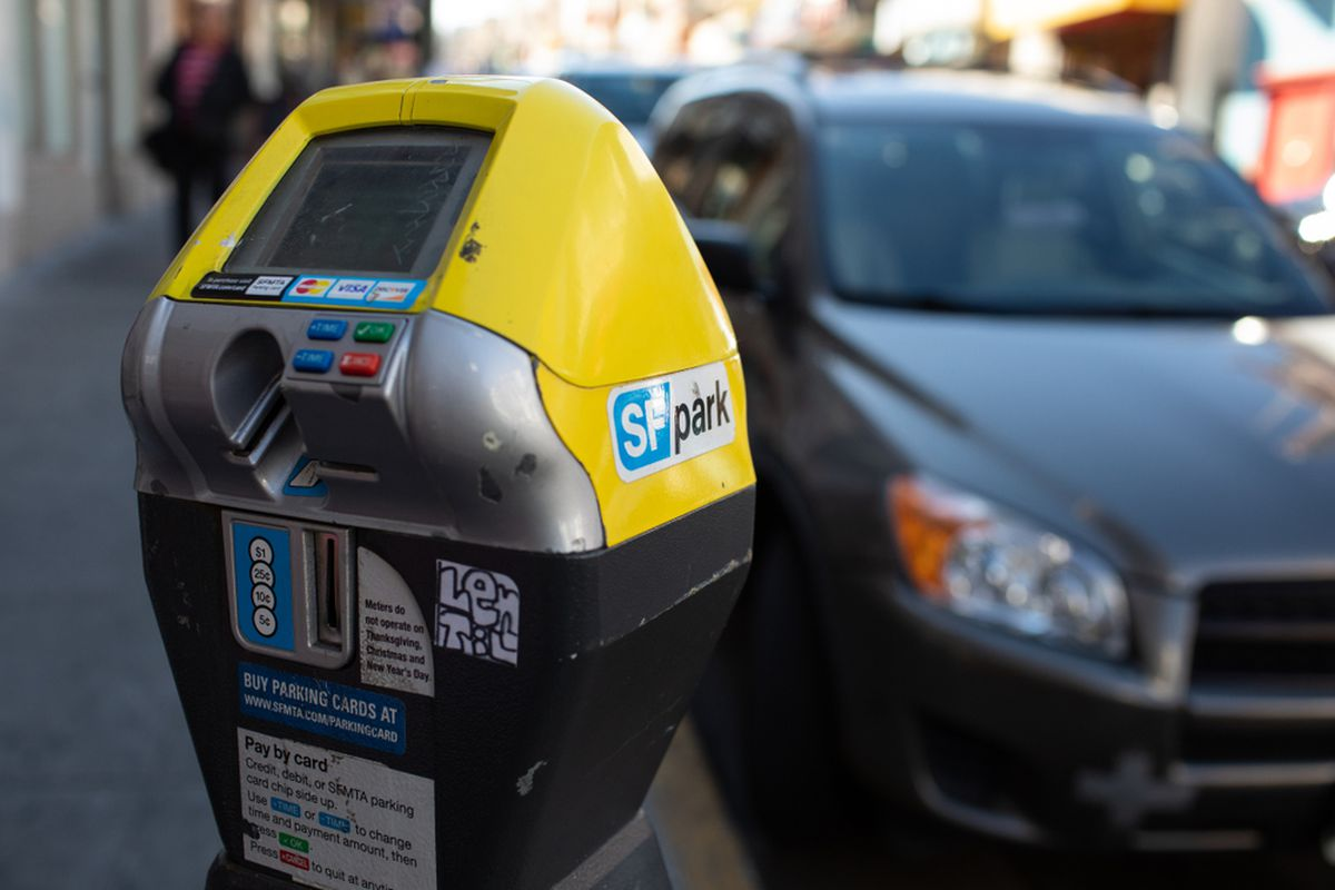 A closeup of a yellow parking meter with a blue and white SF Park sticker on the side, parked near a black car at the curb.