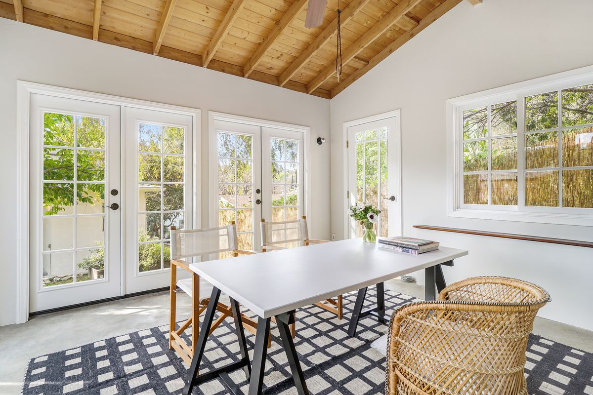 A small room with glass doors and large windows, furnished with a rectangular table and chairs