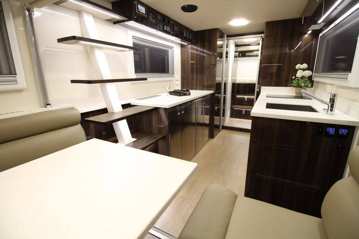The interior of an oversized RV has white counters and dark glossy cabinets in the kitchen, a gray dinette, and stairs leading to the second story.