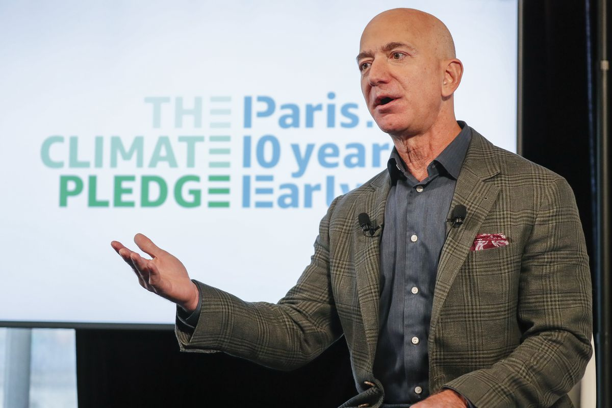 """Jeff Bezos speaks in front of a screen that reads """"The Climate Pledge"""""""