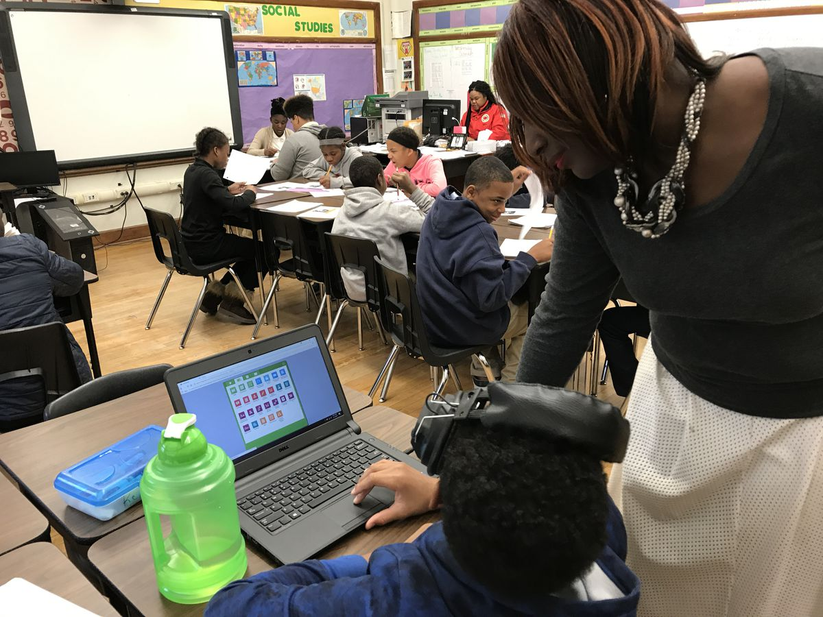 Principal Alisanda Woods talks with a sixth-grade student at Detroit's Bethune Elementary-Middle School about an online learning tool he's using.