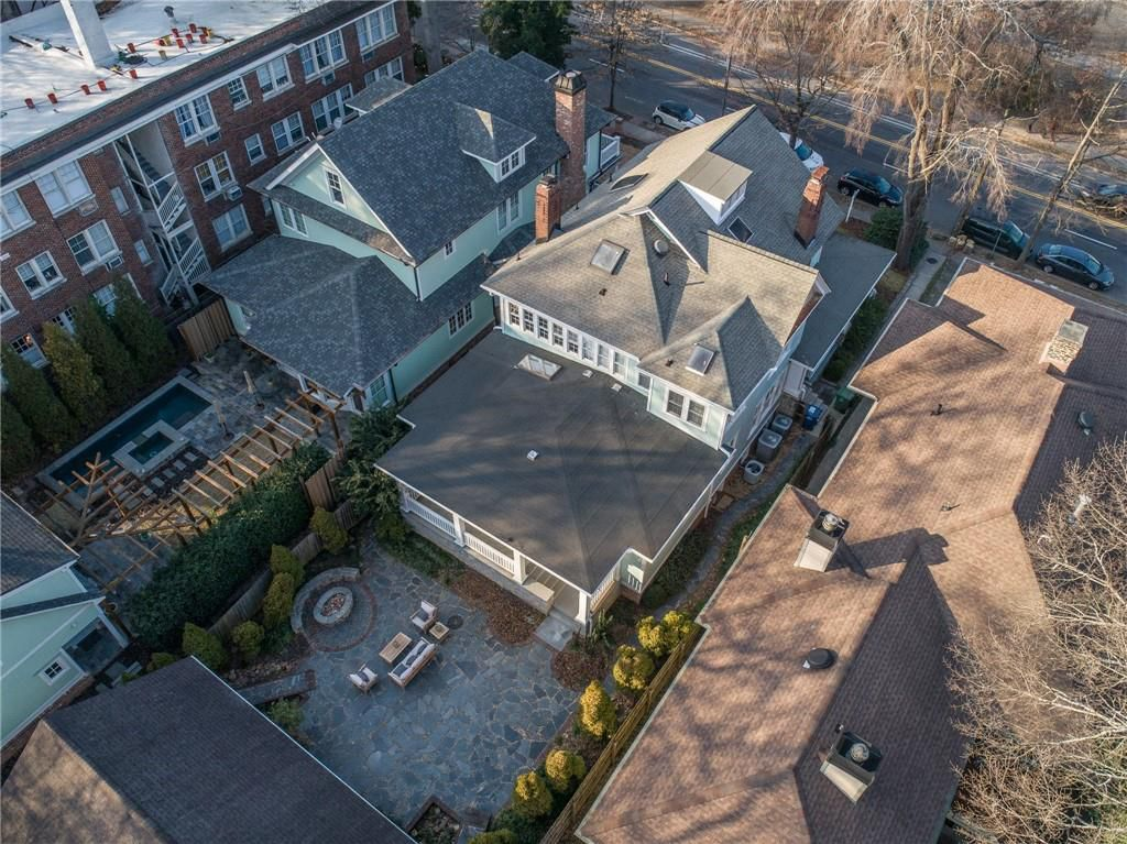 A drone image of a large home with a fire pit in the backyard.