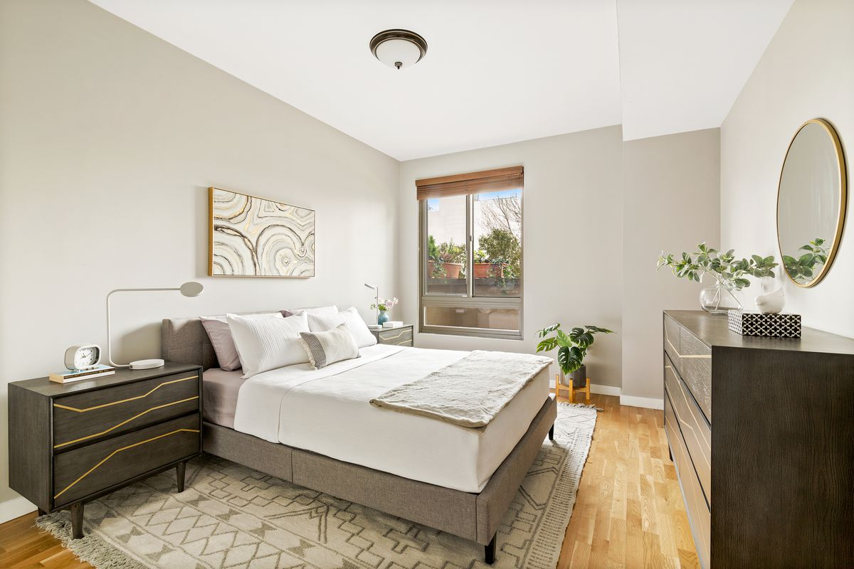 A bedroom with a medium-sized bed, hardwood floors, a window, and grey walls.