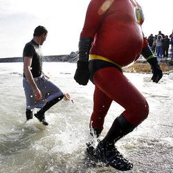 """Josh Hensley, right, """"Mr. Incredible,"""" slogs out of Utah Lake after taking part in the second Polar Plunge at Utah Lake Saturday, a fundraiser for Special Olympics Utah. More than 100 people took the plunge."""