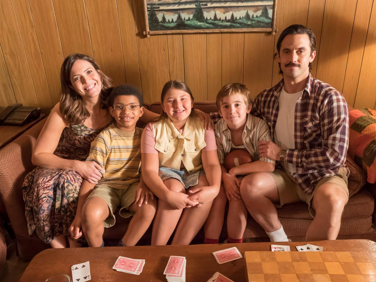 A family from the television show This is Us sitting on a couch in front of a wood paneled wall. There is a man, woman, and three children.