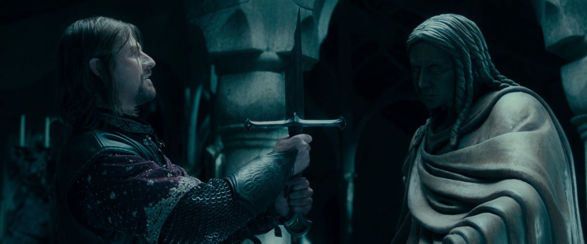 Sean Bean as Boromir lifts the broken sword Narsil with a slight smile in The Fellowship of the Ring