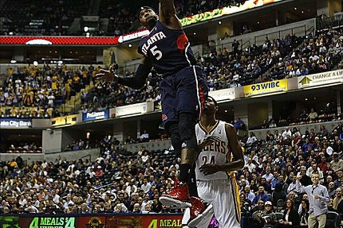 Mar 6, 2012; Indianapolis, IN, USA; Atlanta Hawks forward Josh Smith (5) dunks against Indiana Pacers forward Paul George (24) at Bankers Life Fieldhouse.  Mandatory Credit: Brian Spurlock-US PRESSWIRE