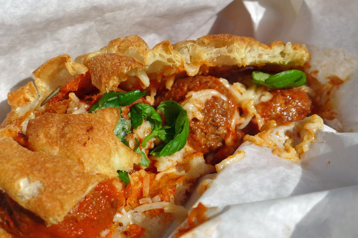 A sandwich on a split rectangular slice of focaccia, with meatballs and basil bulging out.