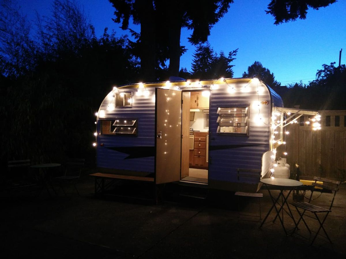 A small, older-style camping trailer in a backyard with a wood fence. It's nighttime, and string lights are wrapped around the trailer.