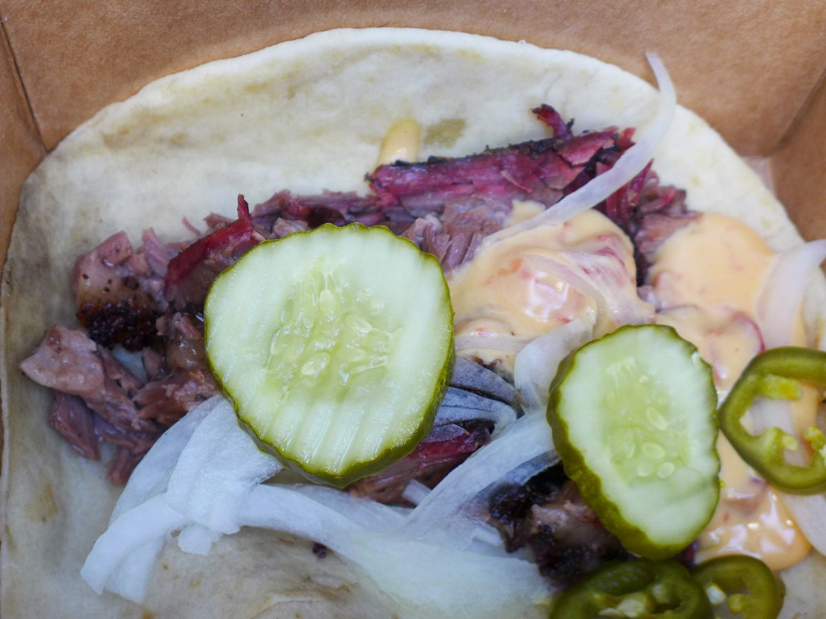A flour tortilla cradling beef brisket, pickles, and onions.