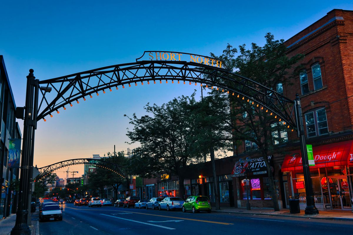 Metal arches frame a road lined with shops and restaurants.