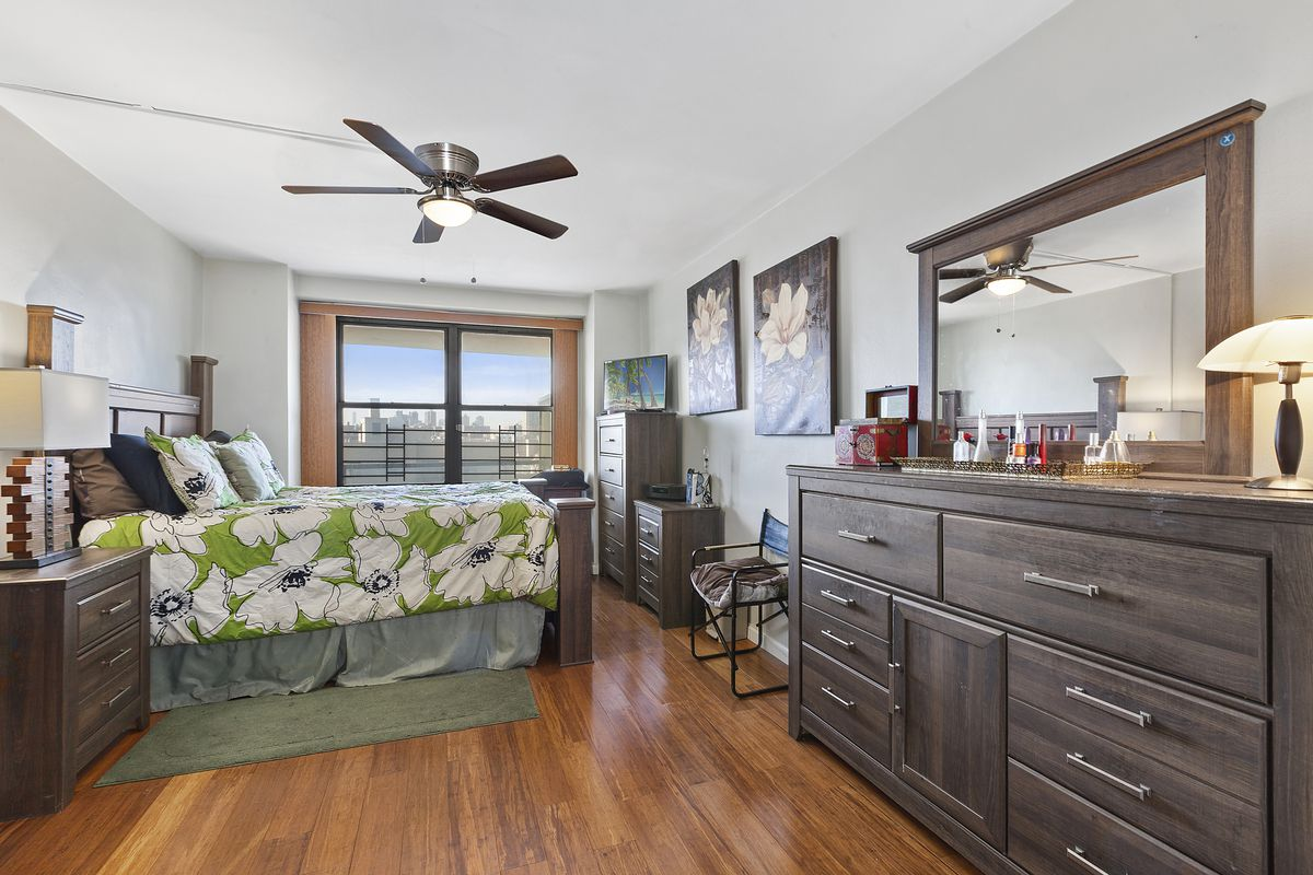 A bedroom with hardwood floors, a large window, a ceiling fan, and wooden furniture.