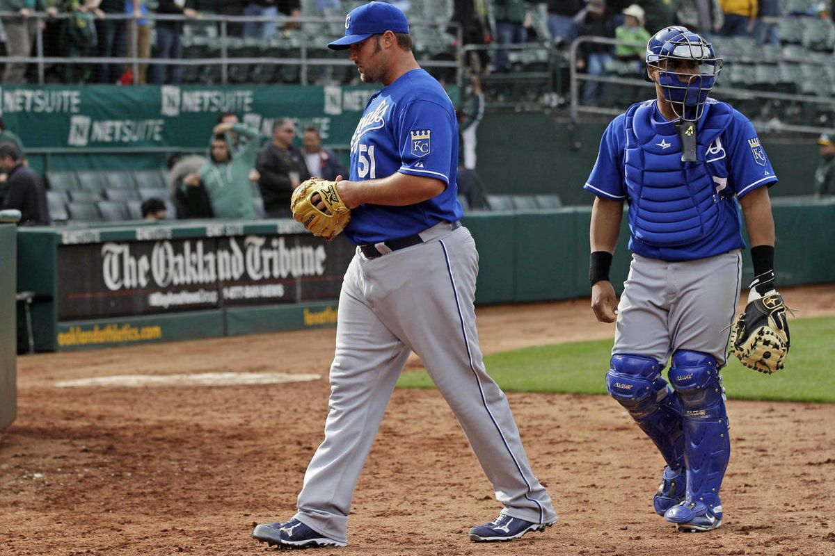 Kansas City Royals relief pitcher Jonathan Broxton walks off the field with catcher Brayan Pena after Broxton hit Oakland Athletics' Jonny Gomes with a pitch with the bases loaded during the 12th inning of a baseball game Wednesday, April 11, 2012, in Oak