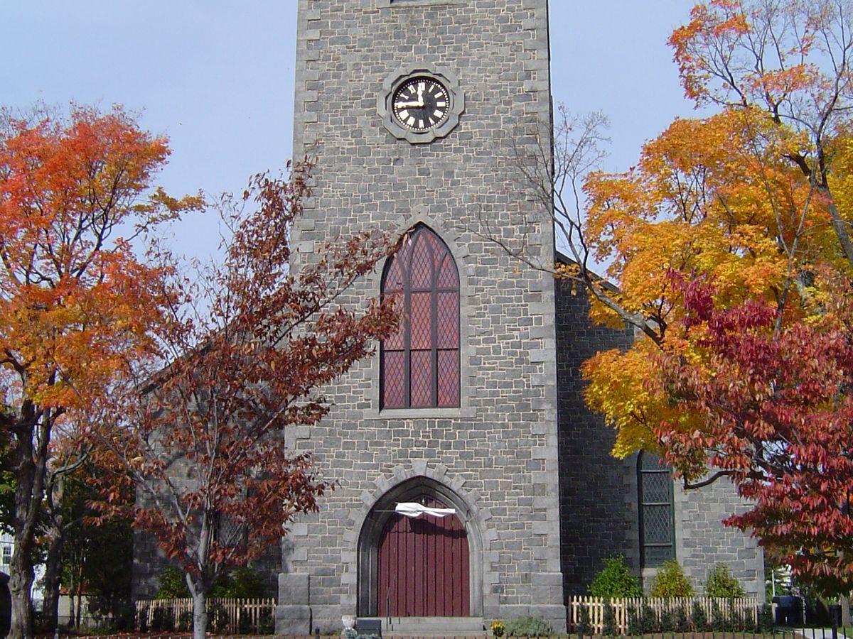 A narrow stone church with a tall steeple.