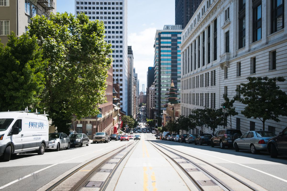 A shot of downtown San Francisco with the Oakland Bay Bridge standing between two rows of buildings and cable car tracks in the center of the street.