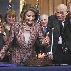 House Speaker Nancy Pelosi of Calif. blows her birthday cake during a bill enrollment ceremony on Capitol in Washington, Friday. The bill amends the recently enacted health care law. Rep. John Dingell, D-Mich., is at right.