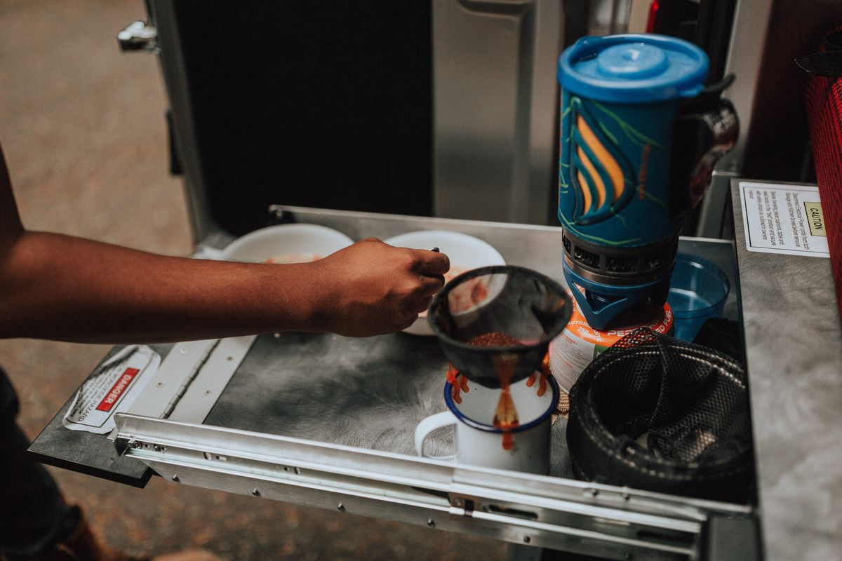 A person making coffee with a portable coffee maker on a shelf in a camper van.