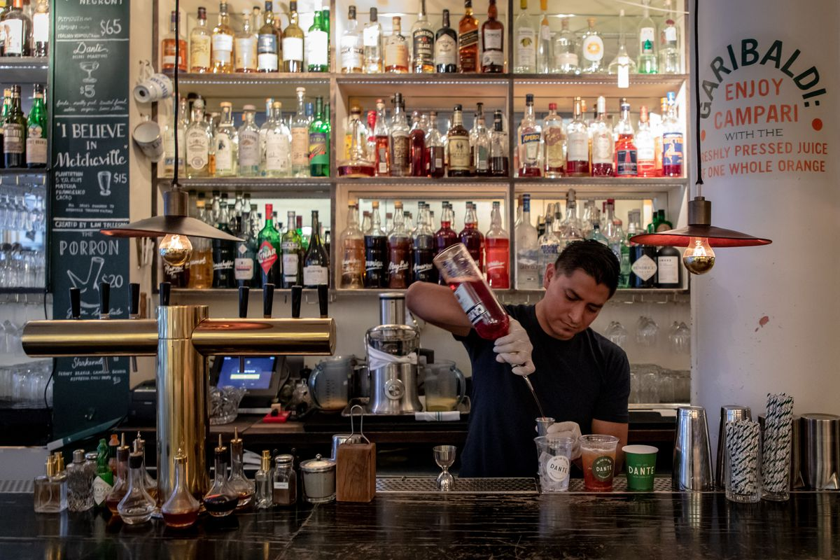 A bartender pours a drink standing behind a bar counter