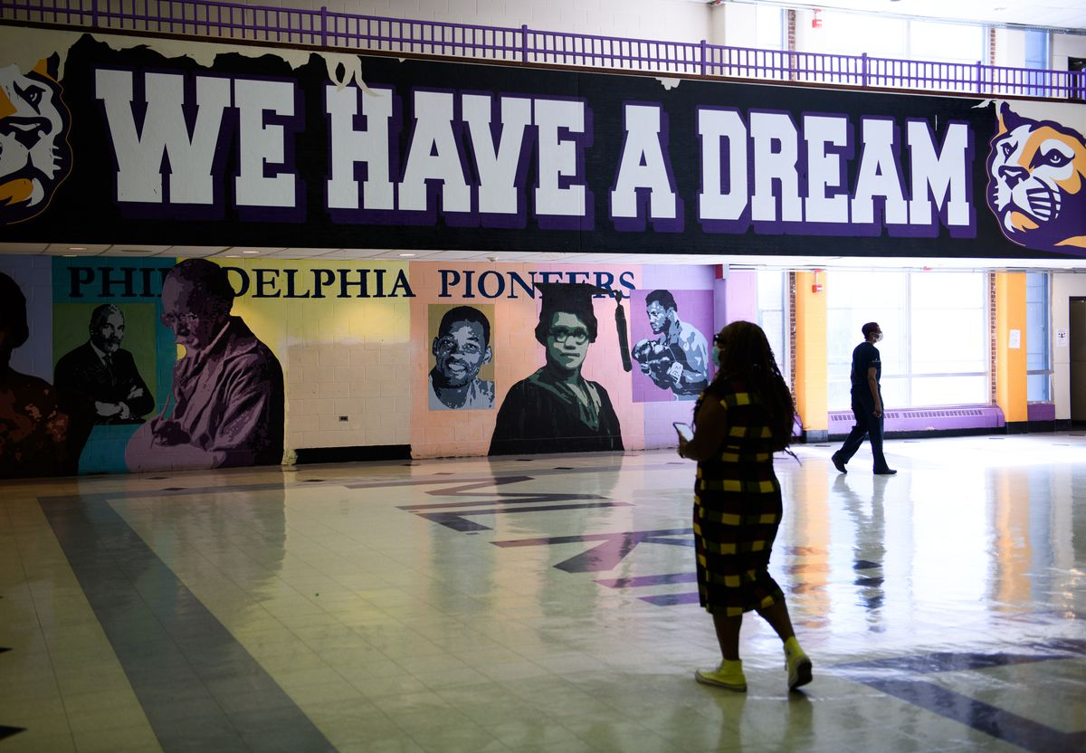 """A school official walks in front of a sign in a cavernous hall that reads """"We Have a Dream."""""""