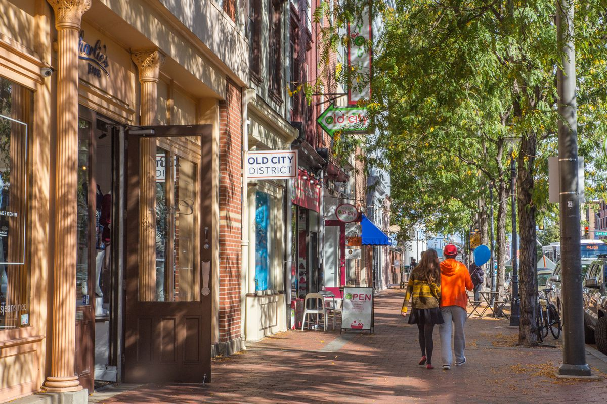 A couple walking down a sidewalk in Old City.