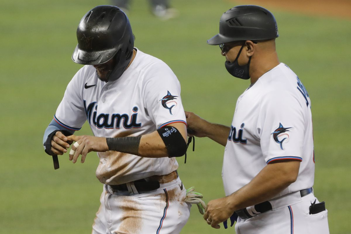 Miami Marlins shortstop Miguel Rojas (19) reacts after a finger injury during the eighth inning of the game against the Philadelphia Phillies at loanDepot Park