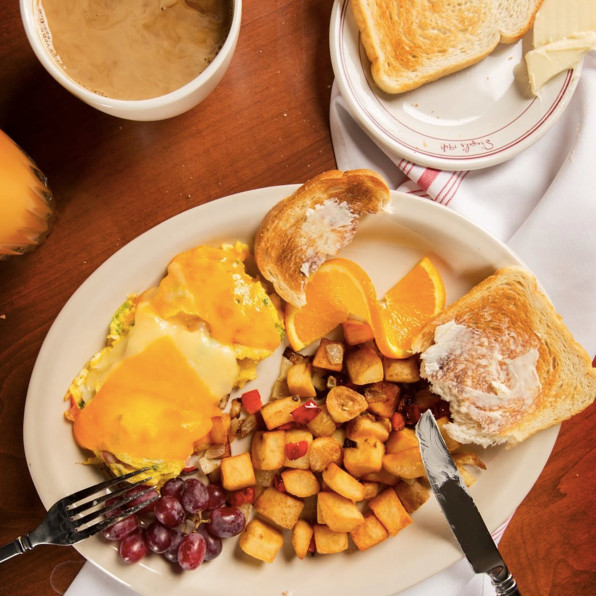 Eggs with cheese, potatoes, toast, and grapes
