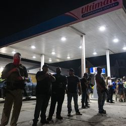 A group of armed individuals stand in front of Ultimate Convenience Center on Sheridan Road during a protest over the shooting of Jacob Blake, Tuesday, Aug. 25, 2020, in Kenosha, Wis.