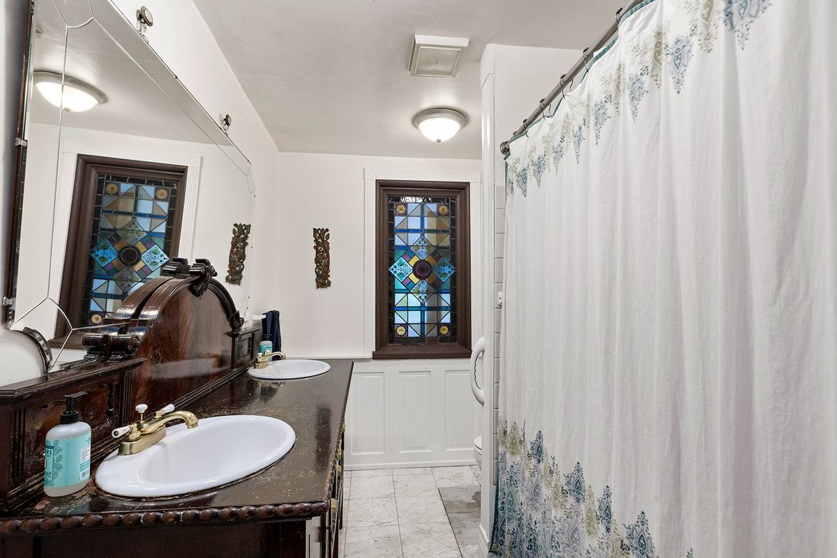 A long white bathroom with a blue shower curtain.