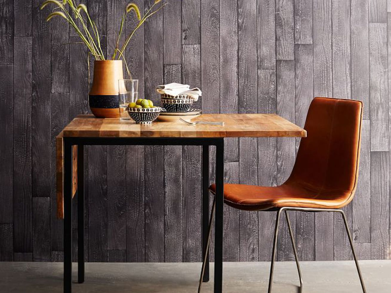 A wood and metal table sits next to a leather chair.