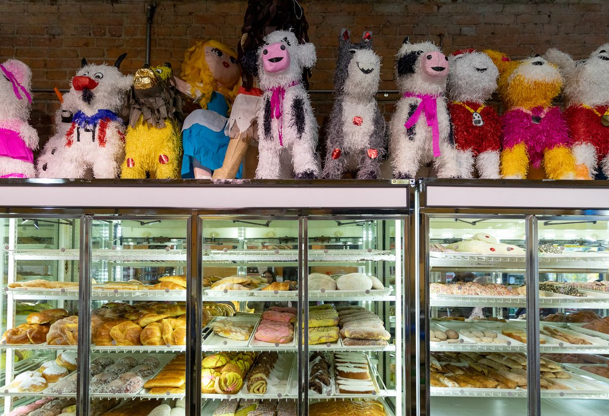 Pinatas sit on top of big glass pastry cases full of colorful Mexican breads and cookies.