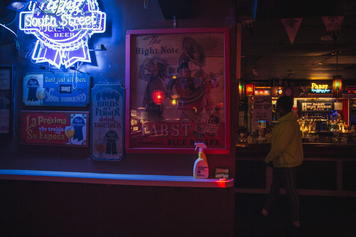 inside of dive bar with neon signs and bottle of cleaner