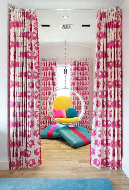 A soft pink room with bright, pink-flowered curtains.