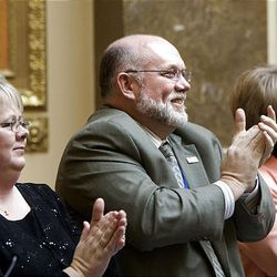 """Representative Kory M. Holdaway and his wife Debbie, left clap along with the song """"Utah Man"""" as it is sung by the babershop quartet Rimson 4 at the start of the 2009 session of the Utah Legislature at the Capitol building in Salt Lake City, Monday."""