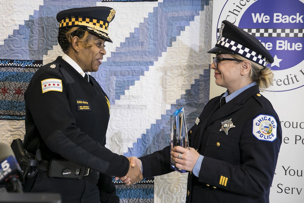 Cmdr. Crystal King-Smith presents Officer Lucyna Murawski with an award by the Chicago Police Memorial Foundation for assisting in the birth of twin girls on Nov. 1 at the Red Line's Roosevelt Road station during a ceremony at the Chicago Patrolmen's Fede