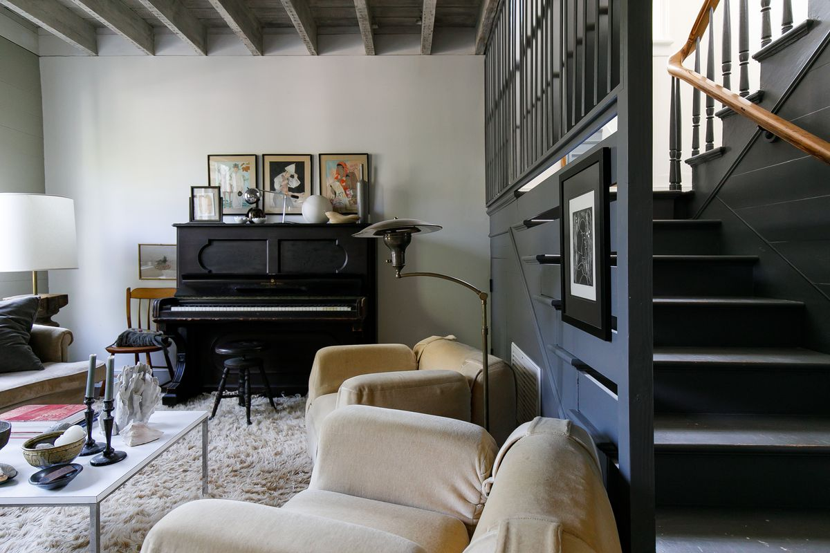 A living room with an upright piano, two armchairs, a table, and a couch. There is artwork above the piano. There are various ornamental objects on the table. To the right is a staircase.