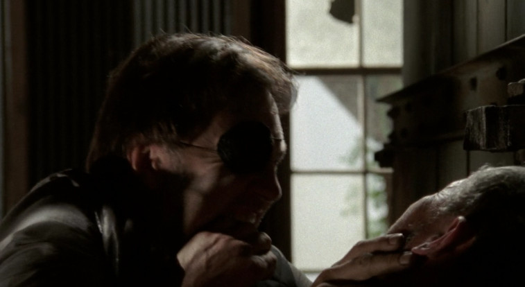 A man with an eye patch is choking another man. They are both in a warehouse.
