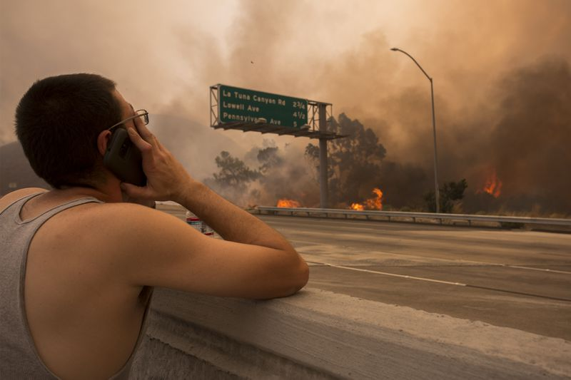 A man watches to see if his house and two of his cats on the other side of thick smoke and flames might burn near the community of Tujunga during the La Tuna Fire on September 2, 2017 near Burbank, California.